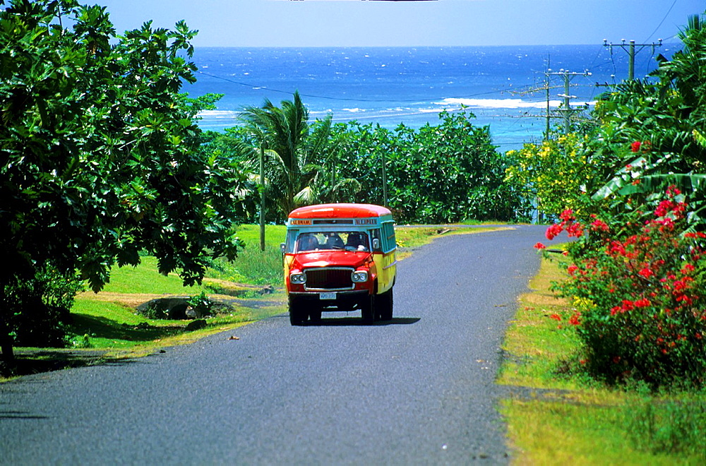Typical painted bus on a small highway on Samoa islands