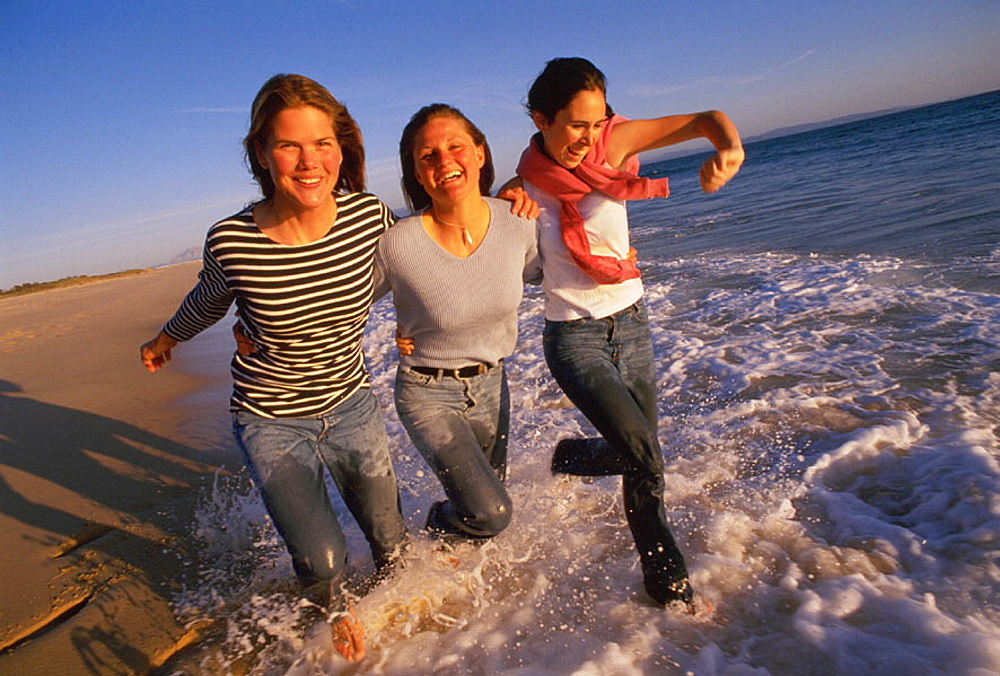 Three women running at the beach