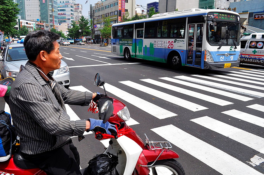 Busan, South Korea, a man crossing the zebra on a motor-bike near the Jagalchi Market