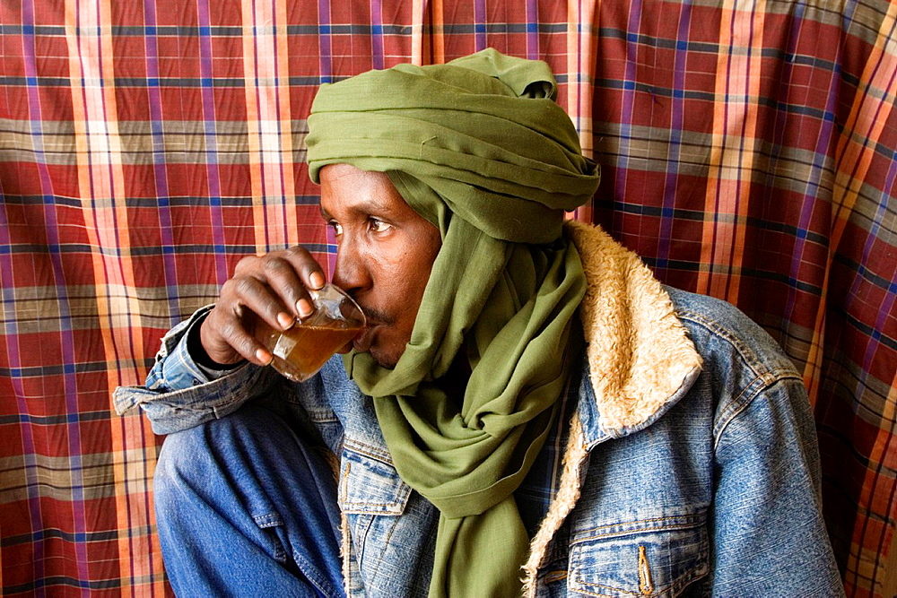 Tripoli, Libya, Ali, a Tuareg Tailor, Stops for Tea in Tripoli Medina Old City His dress combines traditional male veil tagulmust with Western denim jacket