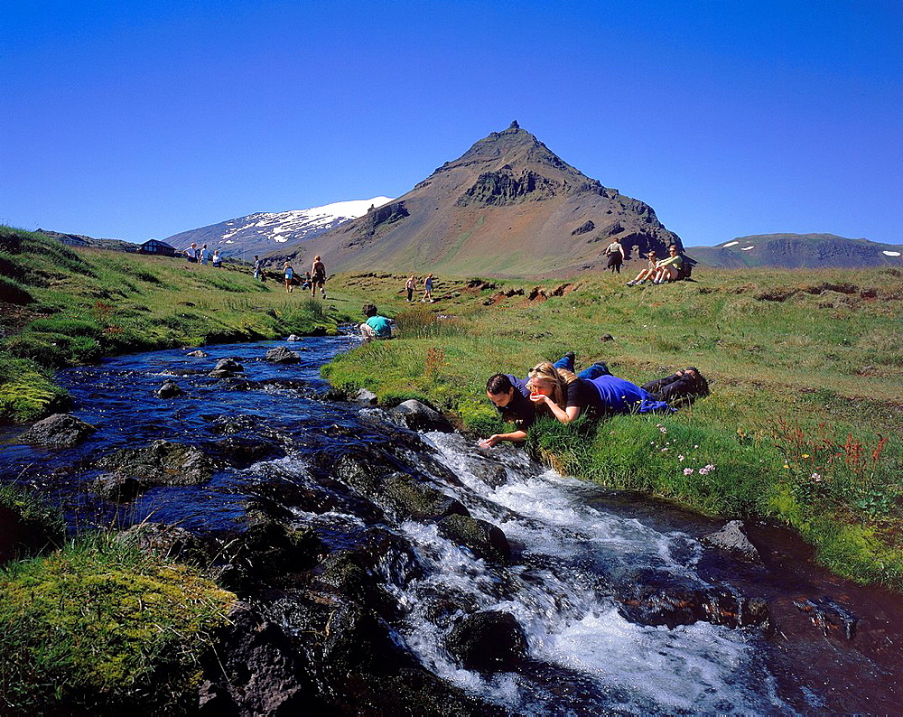Hikers Drinking from Stream in Iceland Couple drinking fresh water from a creek near the Snaefellsjokull glacier on Snaefellsnes peninsula, Western Iceland