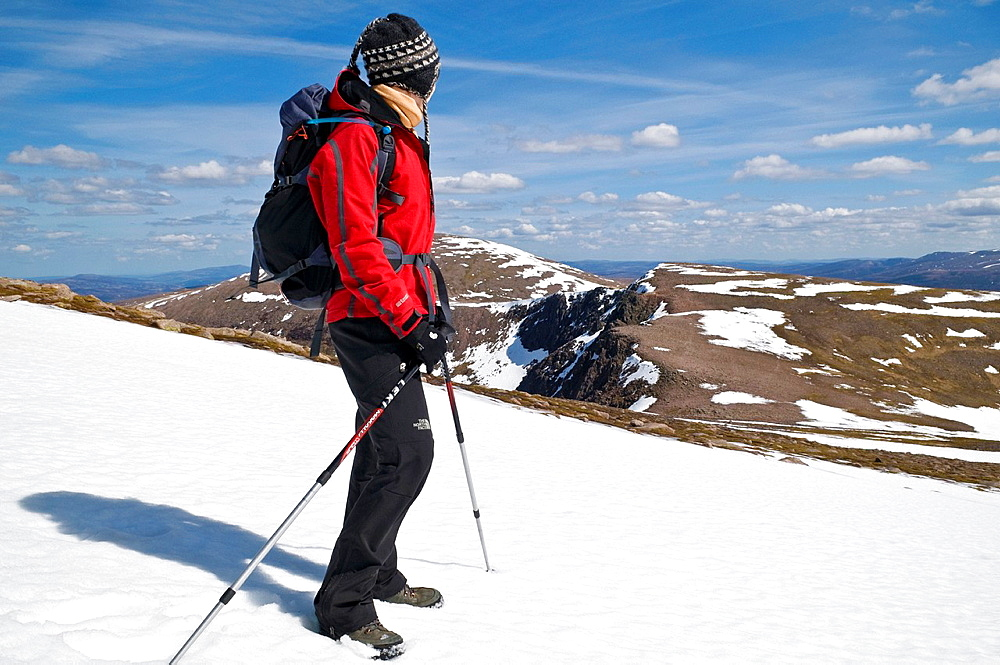 Female hiker takes in view of Cairngorms from Cairn Lochan on spring day, Highland, Scotland