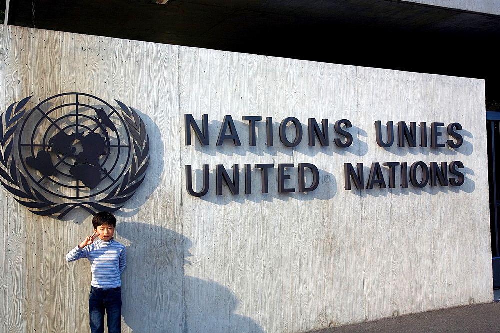 Boy posing in front of United Nations HQ Sign in Geneva