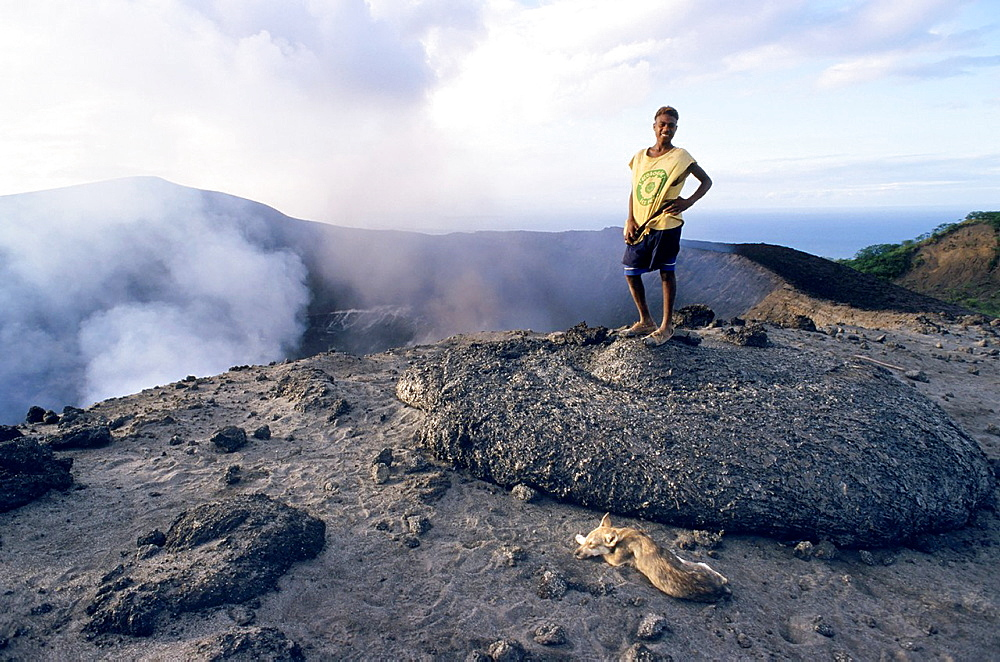 Local guide standing up on a freshly dropped lava bomb near the crater, Yasur Volcano, Sulphur Bay, Tanna Island, Vanuatu
