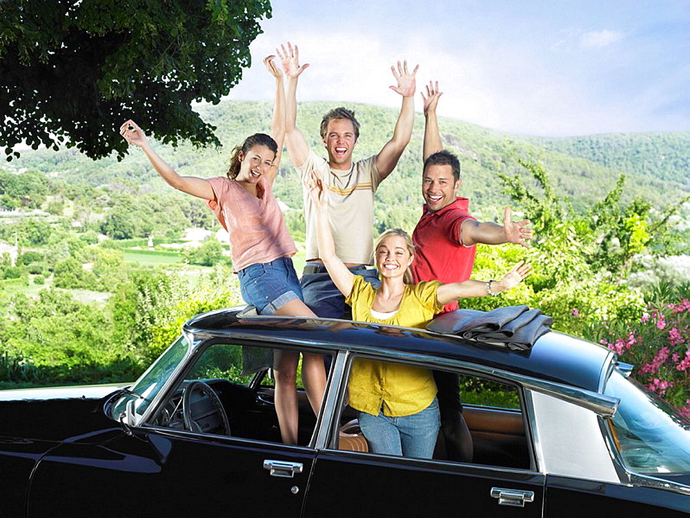 Four friends waving out of car