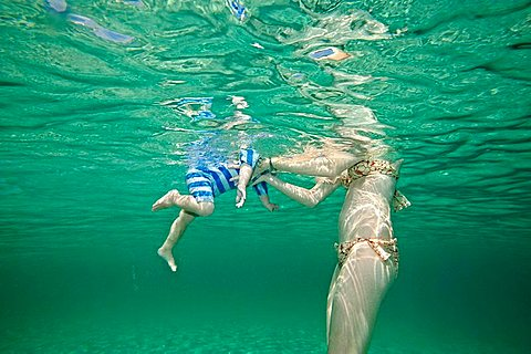 Mother teaching toddler to swim, Woman holding young boy in crystal clear sea, He is swimming, Underwater shot, He is wearing a UV swim suit