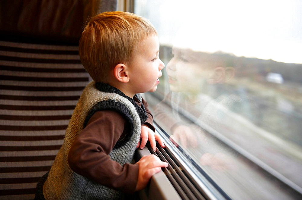 Young boy looking out of train window, Young boy looking out of train window, he is reflected in the window, The train is moving