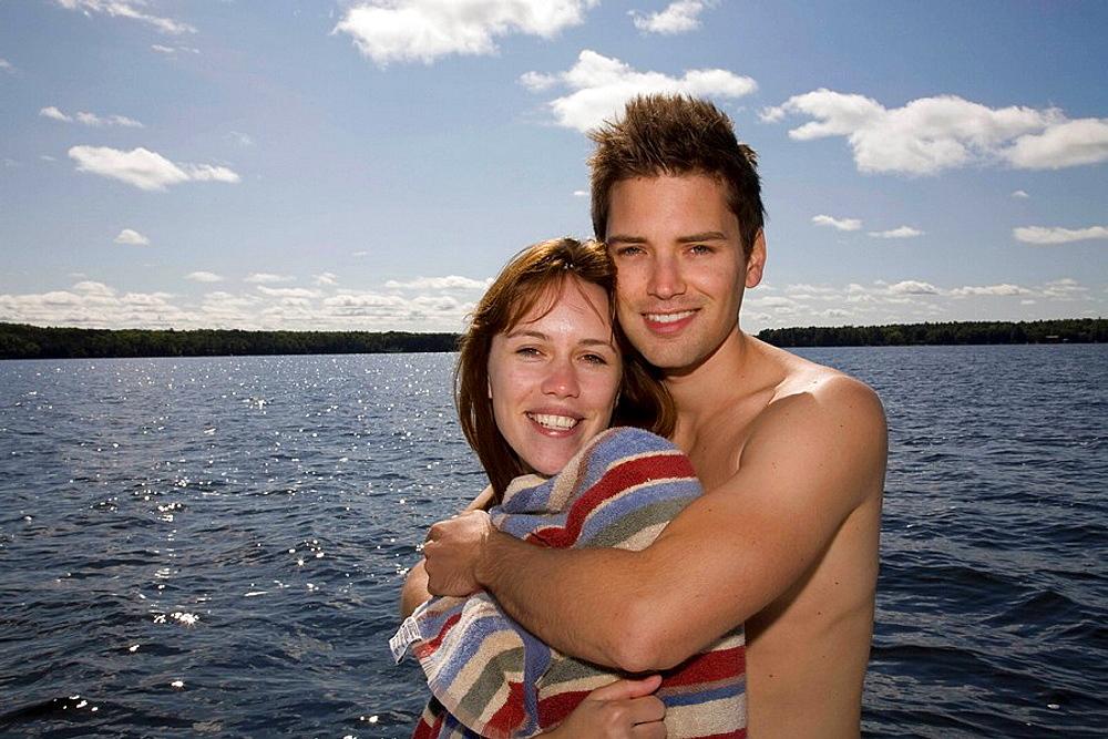 Couple hugging next to lake