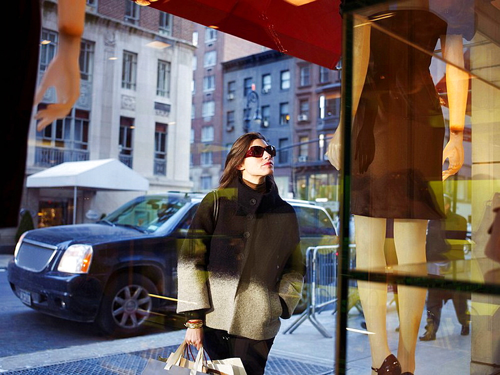 Elegant woman in New York street, Woman in New York street, She is holding shopping bags, looking into shop window
