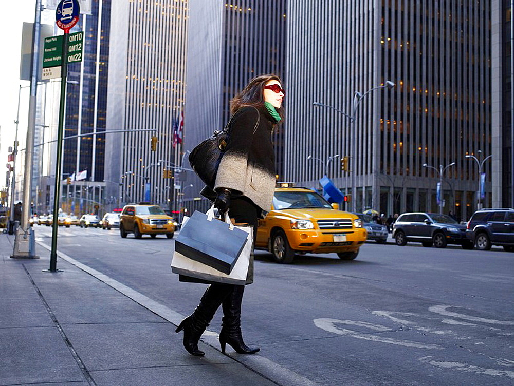 Elegant woman in New York street, Woman in New York street, She is holding shopping bags, looking across road