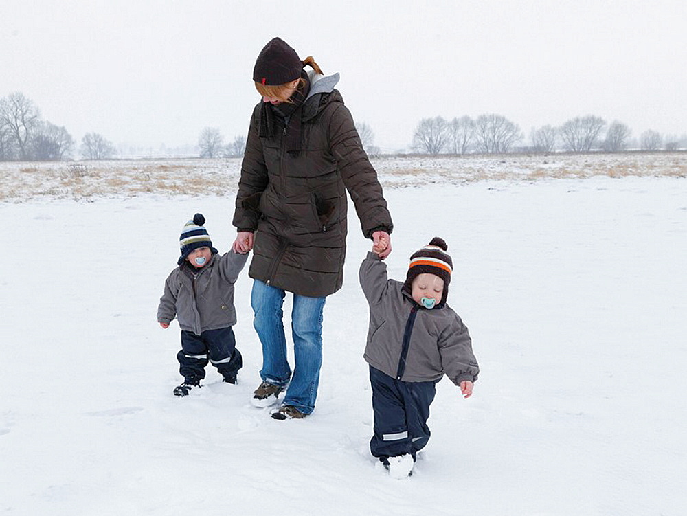 Woman walking with twin sons in snow