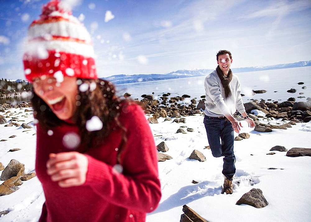 Man throwing snowball at woman