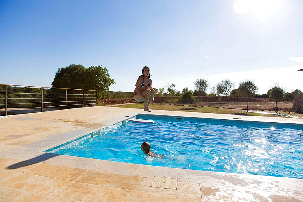 Girl jumping into pool, Girl jumping into pool  doing a cannon ball while boy swims by