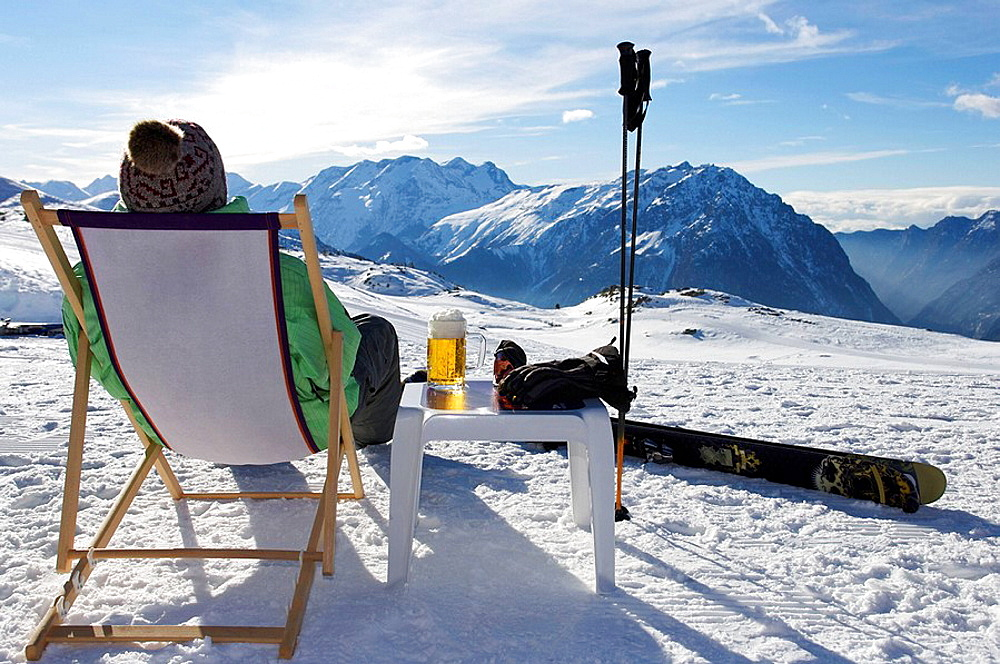 Skier relaxing with a beer, Skier relaxing with a beer on a deck chair on piste