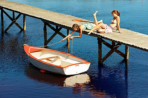 Teenage girls relaxing on jetty, Teenage girls lounging in the sun on jetty with boat