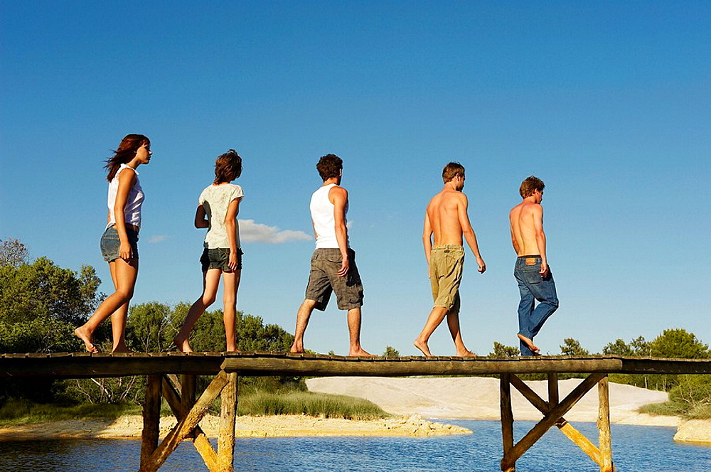 Group of young people walking on jetty, Two teenage girls and three young men are walking in the sun on jetty, Low angle
