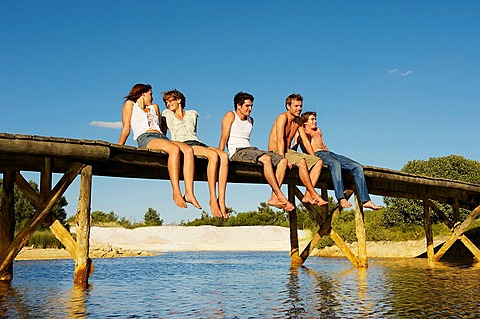 Group of young people sitting on jetty, Two teenage girls and three young men are relaxing in the sun on jetty, they are smiling