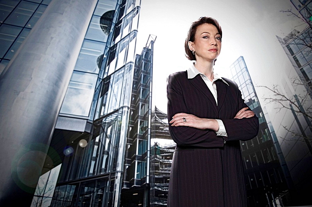 Businesswoman in city setting, direct to camera, confident, arms folded