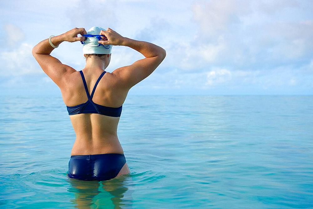 Woman preparing for swim in tropical sea, Woman preparing for swim in tropical sea