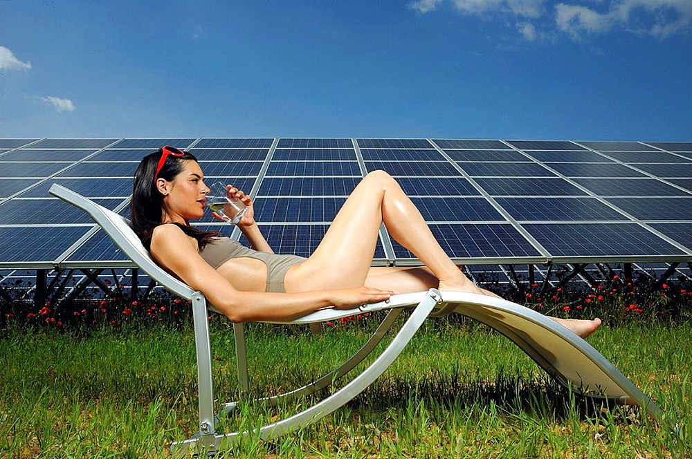 woman sunbathing in front of solar panel, woman sunbathing in front of solar panel