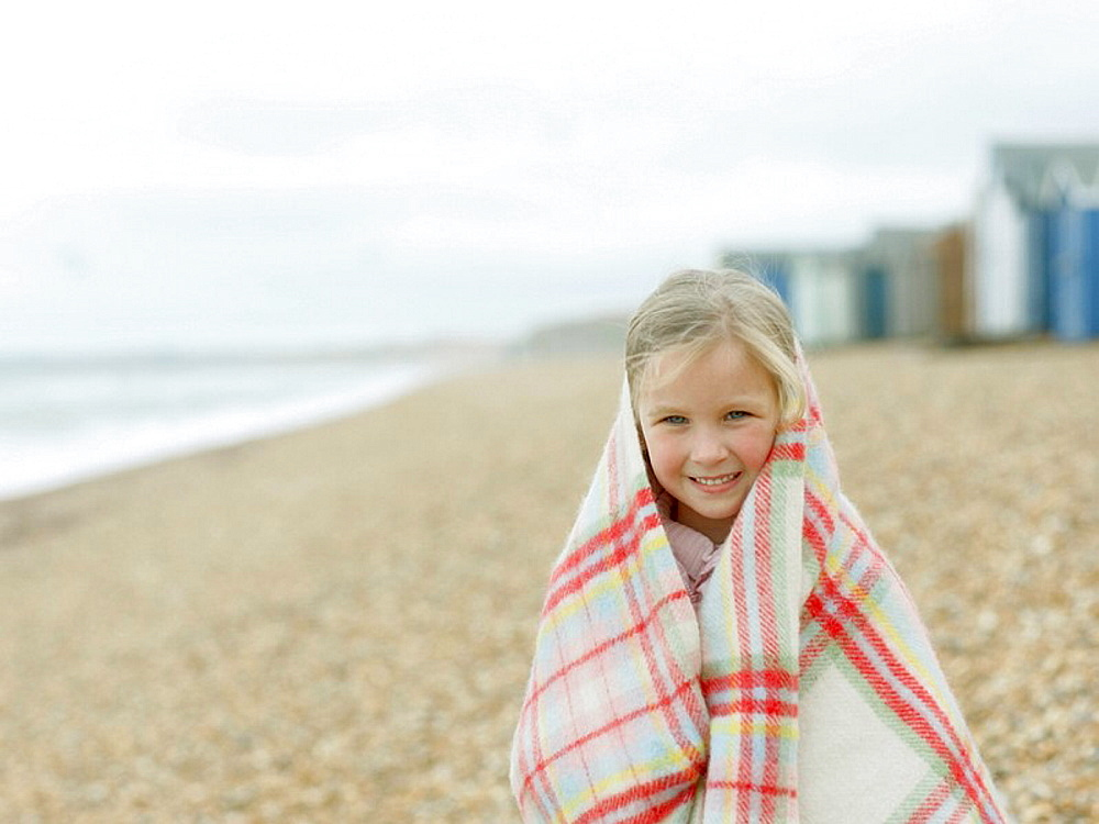 young Girl huddled in Blanket on Beach, young Girl huddled in Blanket on Beach