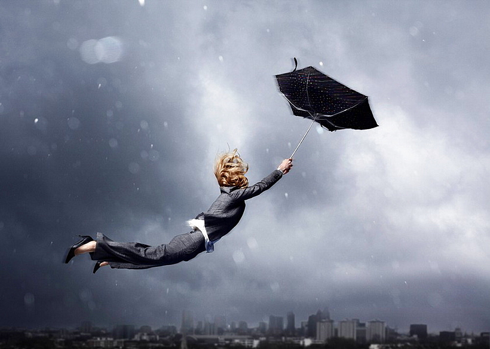 Woman being blown away by an umbrella - 817-337468