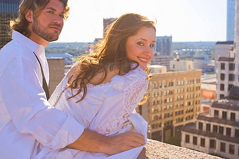 bride and groom on roof top in city