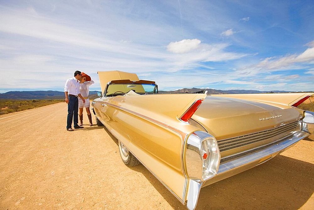 Couple with car trouble in desert, A couple, classic convertible, desert, middle on nowhere