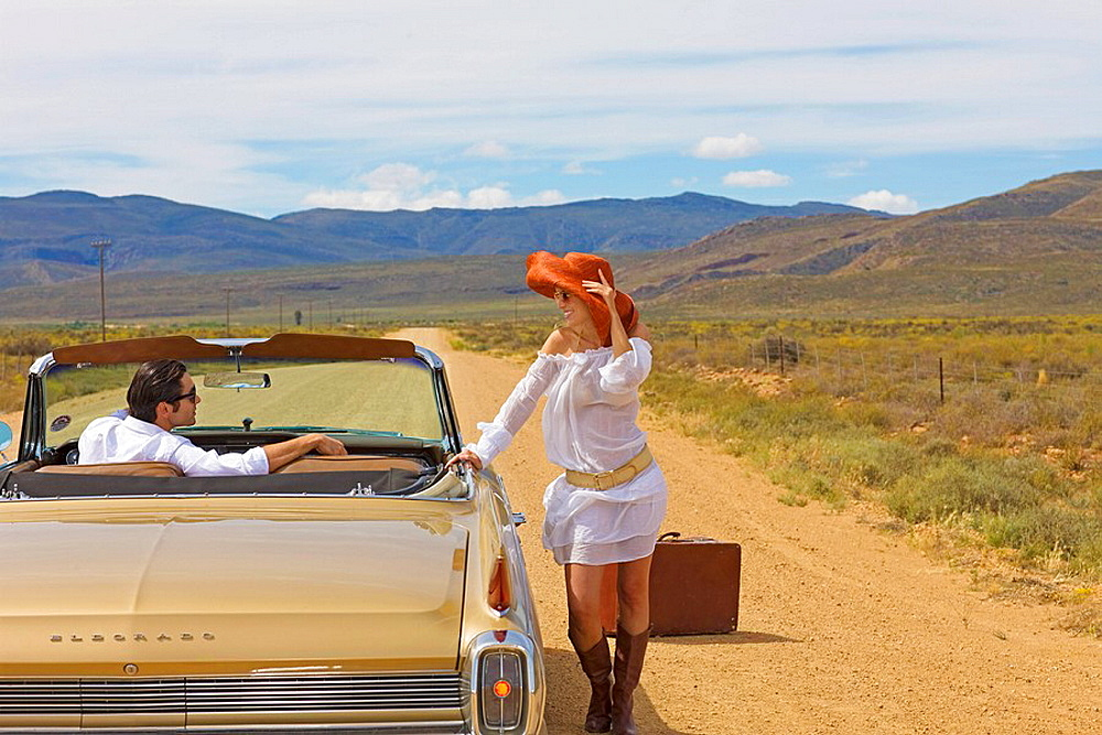 Woman hitching on desert road, Lonely woman on desert road hitch hiking, classic convertible car stops
