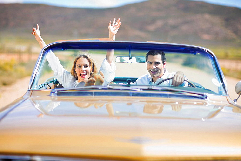 Young couple driving a convertible car, Blond woman, dark haired man, \nclassic convertible car, roadtrip