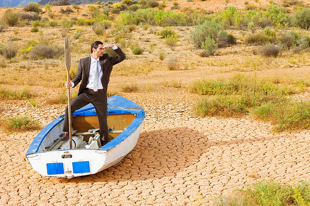 Businessman looking in the distance, Businessman, rowing boat, dry desert