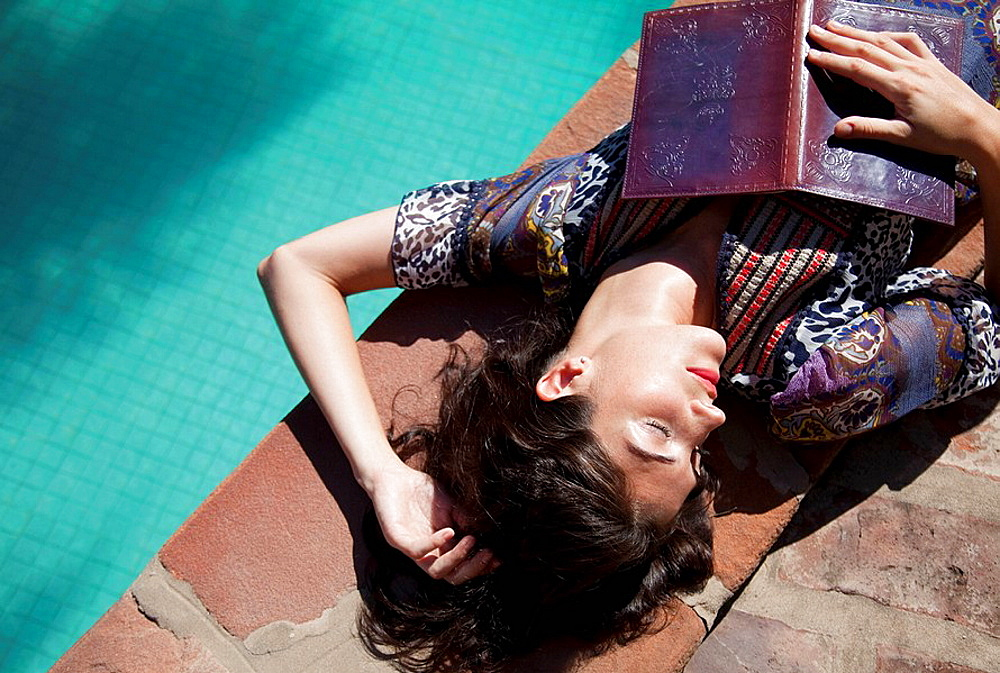 Woman lying at the pool with a book, Woman lying at the pool with a book