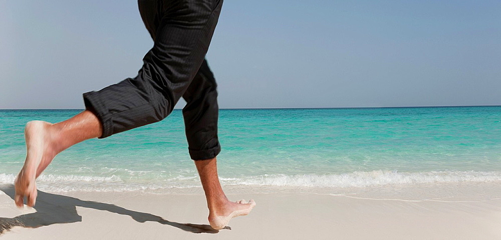 Businessman running on tropical beach, Businessman running on tropical beach