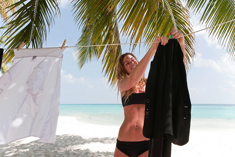 Woman hanging business clothes on beach, Woman hanging business clothes on beach