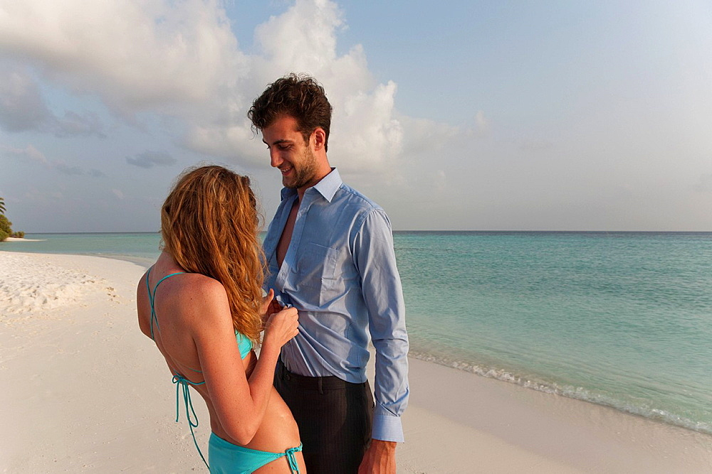 Woman undressing businessman on beach, Woman undressing businessman on beach