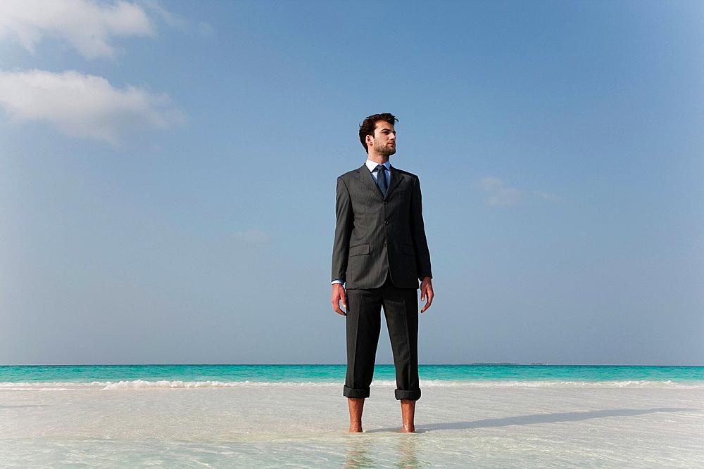 Businessman standing on tropical beach, Businessman standing on tropical beach