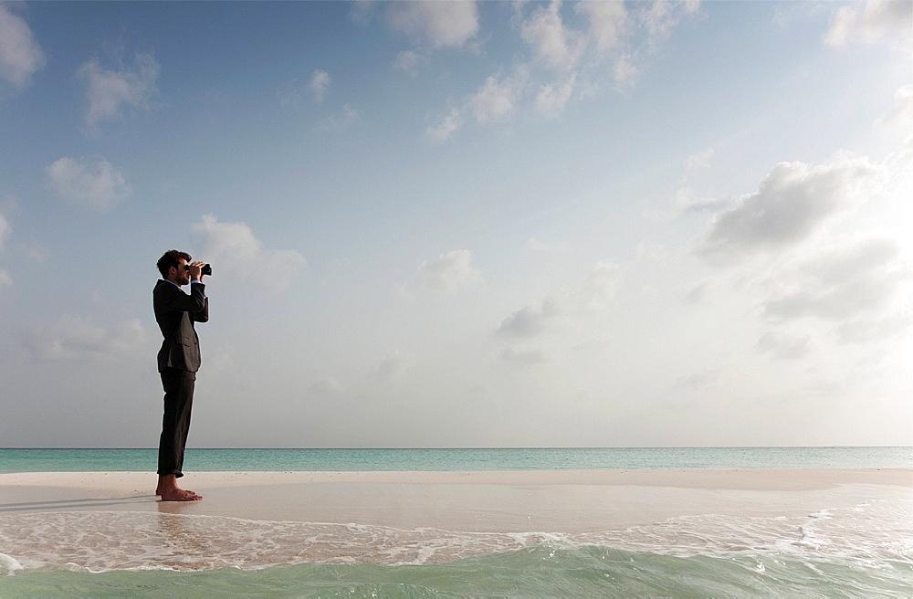 Businessman using binoculars on beach, Businessman using binoculars on beach