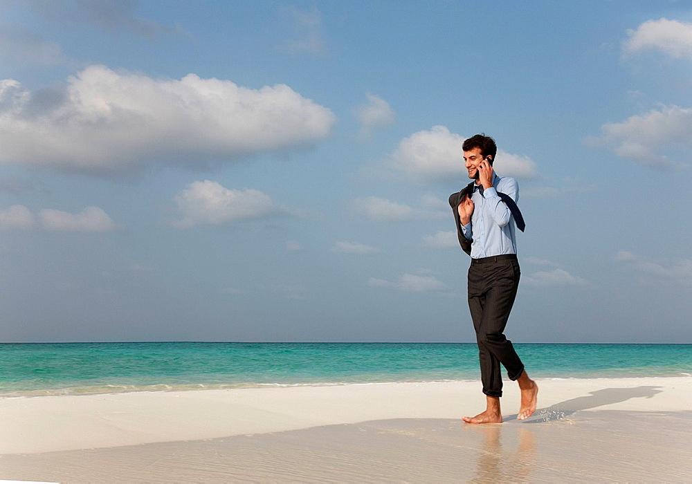 Businessman on cell phone on beach, Businessman on cell phone on beach