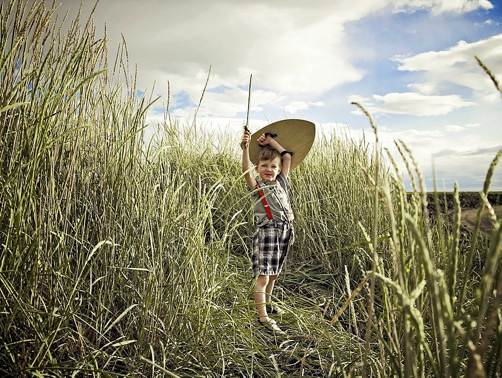 Boy playing with sword in wheat field, Boy playing with sword in wheat field