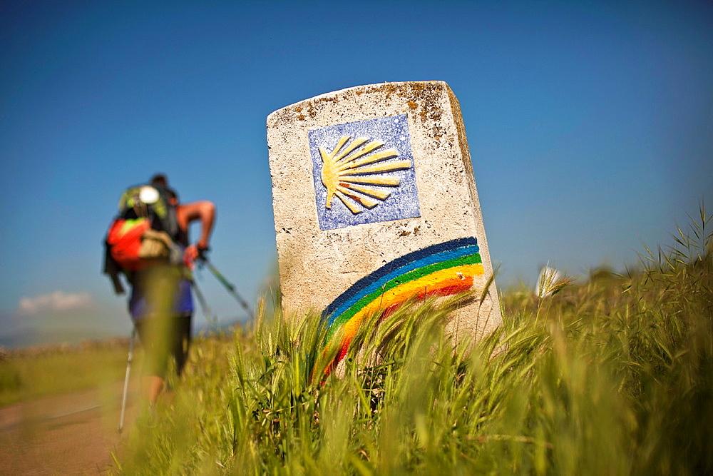 Pilgrim and marker with rainbow along the Camino de Santiago