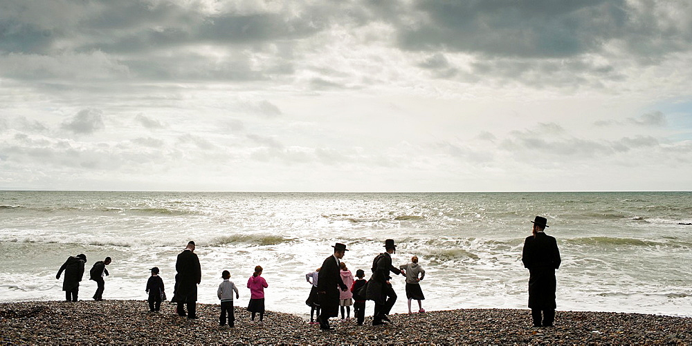 Orthodox Hassidic jews on summer holiday on the beach at Aberystwyth Wales UK