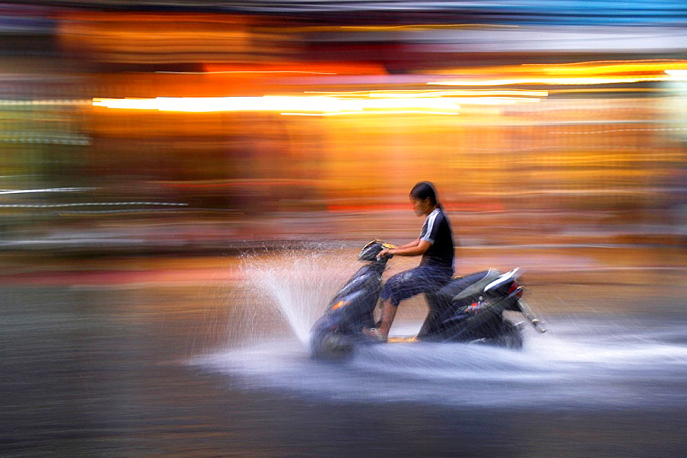 Young woman rides motor scooter at speed in rain along flooded De Tham Street Pham Ngu Lao district Ho Chi Minh City Vietnam - 817-340094