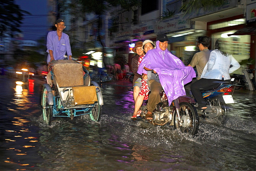 Cyclo rickshaw and motorbikes on flooded De Tham Street Pham Ngu Lao district Ho Chi Minh City Vietnam