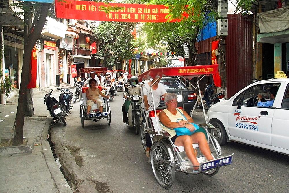 Visitors on cyclo rickshaw group tour of Old Quarter Ma May Street Hanoi Vietnam