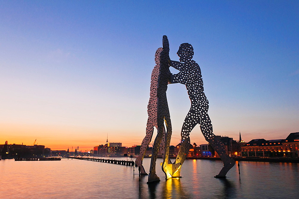 Molecule Man, sculpture by American artist Jonathan Borofsky, staging in the Spree river at sunset, overlooking the Oberbaumbruecke bridge, Friedrichshain and tv tower, Friedrichshain-Kreuzberg, Berlin, Germany