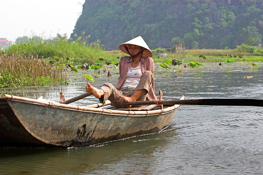 Unusual foot rowing Tam Coc area of Ngo Dong River near Ninh Binh north Vietnam