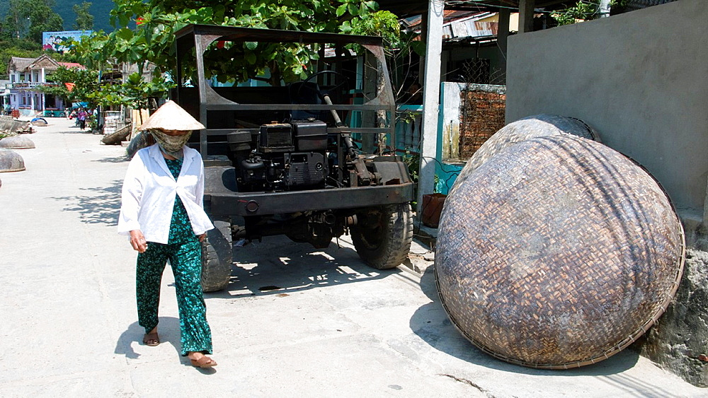 Conical hat woman walks past round coracle boat and motorized truck chassis Cham Island off historic Hoi An Vietnam