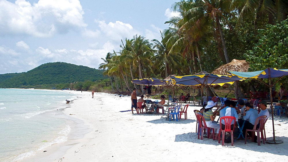 Visitors eat and drink in shade of umbrellas white sand Bai Sao beach south east Phu Quoc Island Vietnam