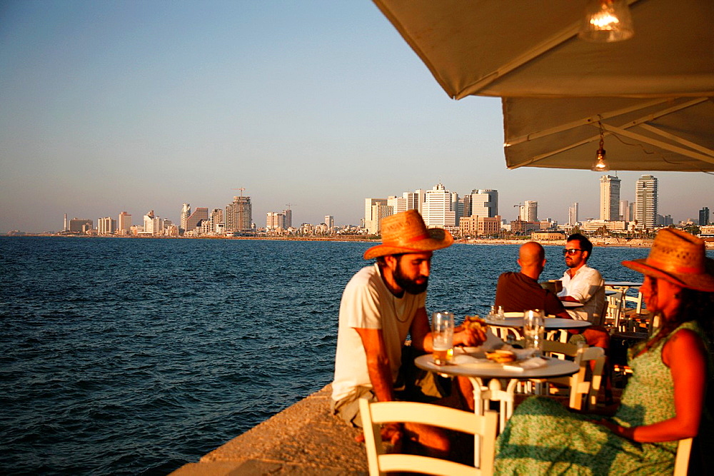People sitting at Casita Bar & Restaurant in Old Jaffa with a view over the sea and Tel Aviv, Israel