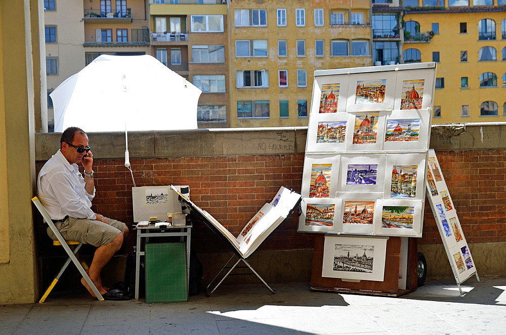 Street painter on the phone, Arno river banks, Florence, Tuscany, Italy